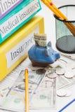 Pulisca la forma, le cartelle, il porcellino salvadanaio ed i soldi di assicurazione Fotografie Stock Libere da Diritti