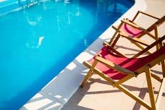 Pulisca la piscina con le sedie prendenti il sole Fotografie Stock