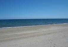 Pulisca la spiaggia di sabbia vuota con cielo blu ed il mare calmo fotografie stock