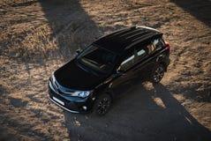 Pulisca SUV nero su suolo desertico asciutto Fotografia Stock