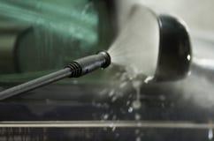 Pulitore ad alta pressione dell'acqua del primo piano come spruzzatura veduta sullo specchio e sulla finestra del lato dell'autom Fotografia Stock