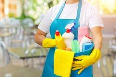 Pulitore con i prodotti di pulizia a disposizione Immagini Stock