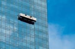 Pulitore di finestra in una gondola che pulisce le finestre immagine stock
