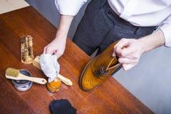 Pulitore di scarpe che usando spazzola per Tan Brogue Derby Boots maschio di lucidatura con crema fotografie stock