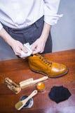 Pulitore di scarpe maschio che usando panno molle per Tan Brogue Derby Boots maschio di lucidatura immagini stock libere da diritti