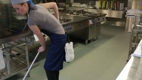 Pulitore di una cucina che pulisce il pavimento stock footage