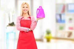 Pulitore femminile che tiene una bottiglia di detergente e che posa a casa Immagini Stock