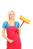 Pulitore femminile che tiene una scopa Fotografie Stock