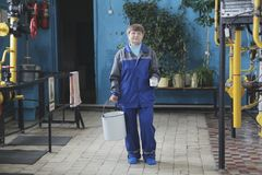 Pulitore sorridente della donna anziana con il secchio vuoto in abiti da lavoro sul sito produttivo fotografia stock libera da diritti