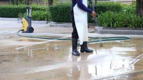 Pulizia all'aperto del pavimento del cemento con il getto di acqua ad alta pressione stock footage