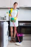 Pulizia allegra della domestica alla cucina Fotografie Stock Libere da Diritti