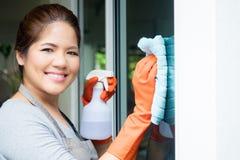 Pulizia asiatica della casalinga sul vetro di finestra Fotografia Stock