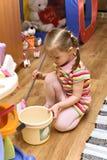 Pulizia della ragazza la sua stanza Fotografie Stock
