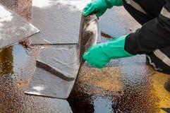 Pulizia di caduta di olio su area di lavoro il pericolo per la natura Fotografia Stock Libera da Diritti