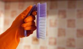 Pulizia di spazzola a disposizione, isolato contro lo sfondo delle mattonelle Fotografie Stock