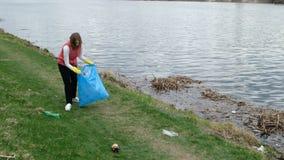 Pulizia volontaria della donna sui rifiuti dal fiume Di raccolto immondizia su all'aperto Concetto dell'ambiente e di ecologia video d archivio