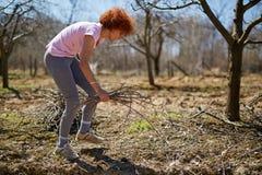 Pulizie di primavera della donna il frutteto Fotografie Stock Libere da Diritti