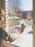 Pulizie di primavera - finestre di pulizia Le mani del ` s delle donne lavano la finestra, pulente immagine stock libera da diritti