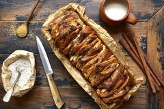 Pull-apart bread with cinnamon and brown sugar.Top view. Pull-apart bread with cinnamon and brown sugar in a baking foarm over old wooden background.Top view Royalty Free Stock Photos
