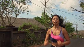 Pull back gimbal shot in dolly style of young exotic fit and beautiful Asian Indonesian woman running on trail road jogging. Pull back gimbal shot in dolly style stock video footage