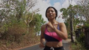 Pull back gimbal shot in dolly style of young exotic fit and beautiful Asian Indonesian woman running on trail road jogging. Pull back gimbal shot in dolly style stock video