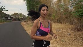 Pull back gimbal shot in dolly style of young exotic fit and beautiful Asian Indonesian woman running on trail road jogging. Pull back gimbal shot in dolly style stock footage