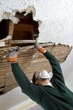 Pull Ceiling Lathe. A young male pulls down plaster ceiling lathe with his hands. renovation. shot from below Stock Photos