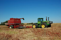 Pull Combine and Green Tractor. A red pull combine and green tractor sit in prairie field with clear blue sky royalty free stock photo