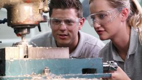 Pull focus shot of engineer training female apprentice to use drill in factory