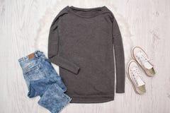 Pull molletonné, espadrilles et jeans gris Fond en bois Concept à la mode, vue supérieure Photo libre de droits