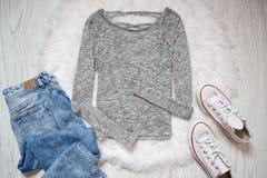 Pull molletonné gris, espadrilles blanches et jeans Fond en bois Concept à la mode, vue supérieure Photographie stock libre de droits