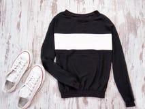 Pull molletonné noir avec une rayure blanche, espadrilles blanches concept à la mode Images stock