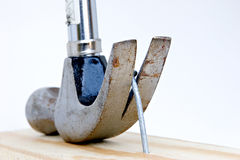 Pull that nail (mistakes happen). Hammer claws pulling a bent nail from a board. White background royalty free stock photos