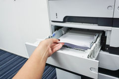 Pull paper from printer tray. Pull piece of paper from the printer tray Royalty Free Stock Photos