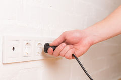 Pull the plug concept with man pulling black cord and plug. Close up royalty free stock images