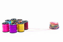 Pull thread out of reel. Pull out many color thread of reels on white   background Stock Photo