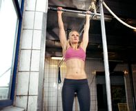Pull Up. Young adult fitness woman preparing to do pull ups in pull up bar Royalty Free Stock Image