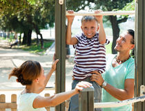On pull-up bar at playground Stock Photos
