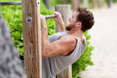 Pull-up strength training exercise - fitness man. Working out his arm muscles on outdoor beach gym doing chin-ups / pull-ups as part of a crossfit workout Royalty Free Stock Photos