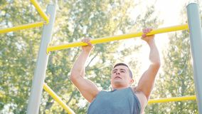 Male Athlet Pull-up Strength Training Exercise. Pull-up strength training exercise. Slim athlete a very fit guy fitness instructor or a personal trainer working royalty free stock photo