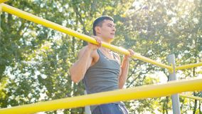Male Athlet Pull-up Strength Training Exercise. Pull-up strength training exercise. Slim athlete a very fit guy fitness instructor or a personal trainer working stock images