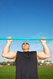 Pull Ups. Strong man doing pull ups on a bar in a field with blue sky in the background Royalty Free Stock Image