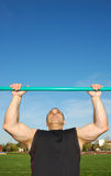 Pull Ups Outdoors. Strong man doing pull ups on a bar in a field with blue sky in the background Stock Photos
