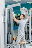 Pulldown. Young sports man has a simulator in the hall. Man with. A beard plays sports Royalty Free Stock Image