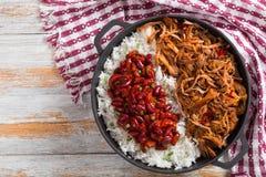 Pulled långsam-lagade mat kött med ris och kyndelvita bönor i tomatsås royaltyfri fotografi