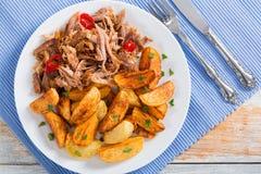 Pulled lento-cozinhou a carne grelhada no forno com as cunhas fritadas da batata imagem de stock