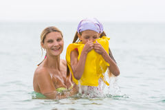 She pulled out of water his seven-year daughter, which closed hand nose in the swimming vest Stock Images