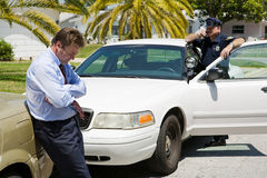 Pulled Over. Embarassed looking businessman pulled over by the police.  Focus is on the businessman Royalty Free Stock Images