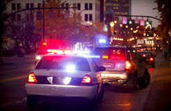 Pulled over by police car. A police officer pulls over a driver for a traffic violation in a downtown city Stock Image
