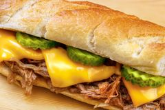 Pulled pork baguette. Sandwich with cheese, cucumber and bbq sauce closeup Royalty Free Stock Photography